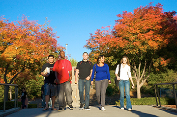 Image of students walking through the fall foliage.